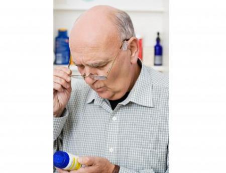 image of man looking at pill bottle under evaluation project of Medi-Cal Managed Care in California