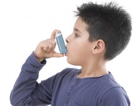 Boy using an asthma inhaler