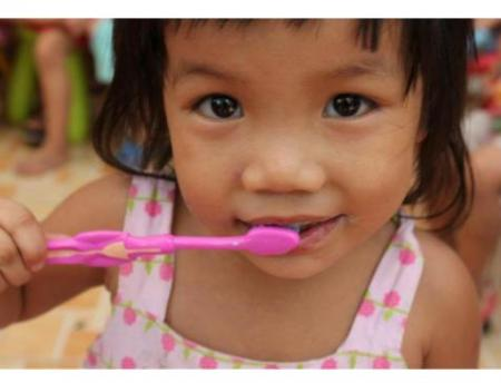 photo of girl brushing teeth under Vietnam Tooth Project